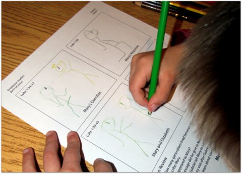 Child's hands drawing stick figures on a Grapevine Studies worksheet