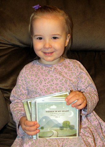 Little girl holding Scripture Lullaby CDs