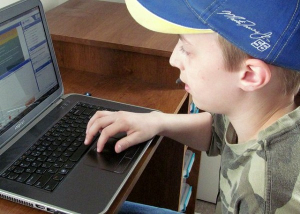Boy using laptop for online science class