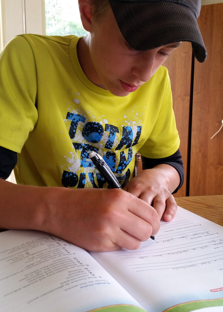 Teen boy writing in science workbook
