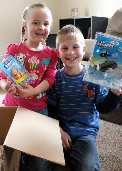 Young brother and sister with packages of Lil Fishys toys