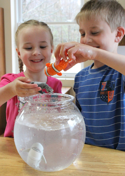 Young brother and sister playing with motorized fish toys in fishbowl