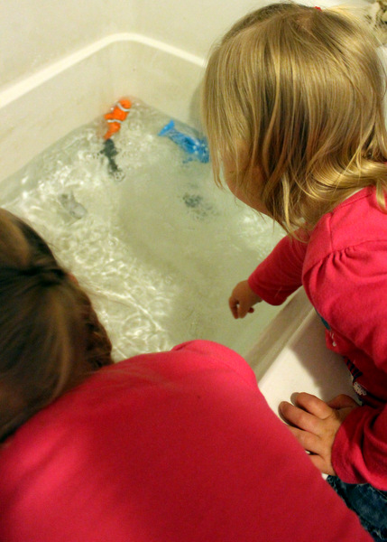 Young sisters playing with fish toys in bathtub