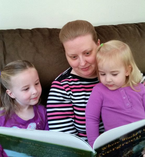 Mother and two little girls reading a book