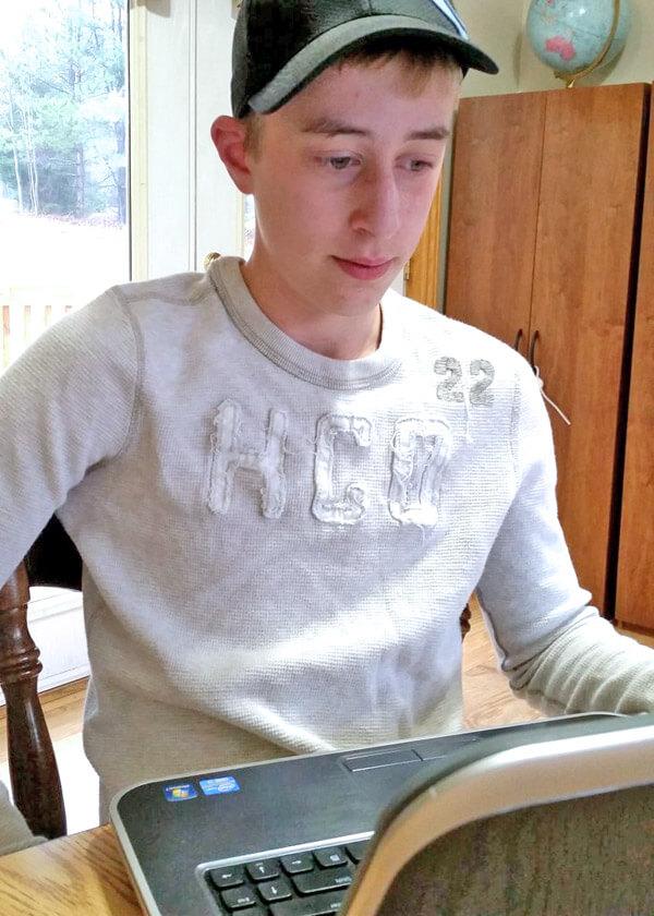 Teenage boy watching Saxon math videos on laptop
