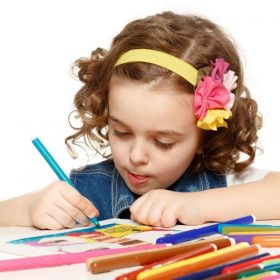 Little girl coloring with markers