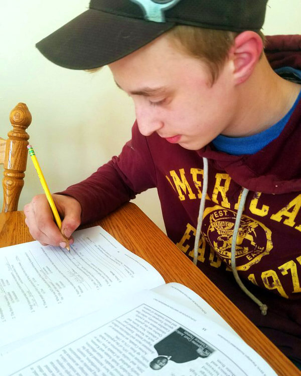Teen boy sitting at table writing in geography workbook