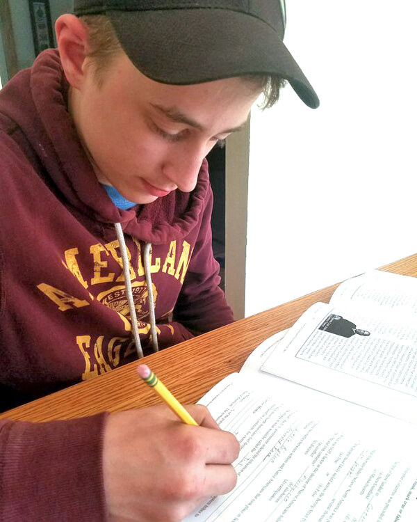 Teen boy sitting at table writing in high school geography workbook