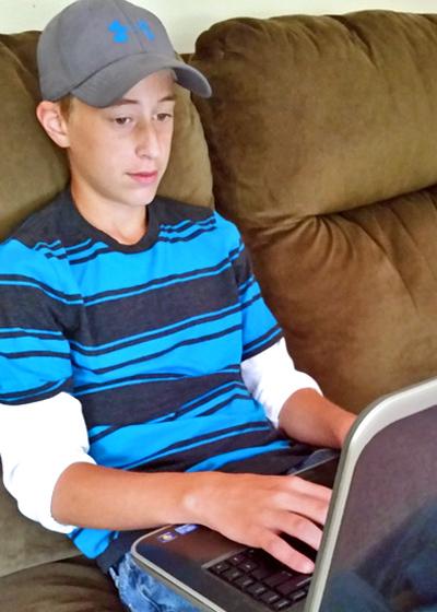 Boy doing a CTCMath lesson on a laptop