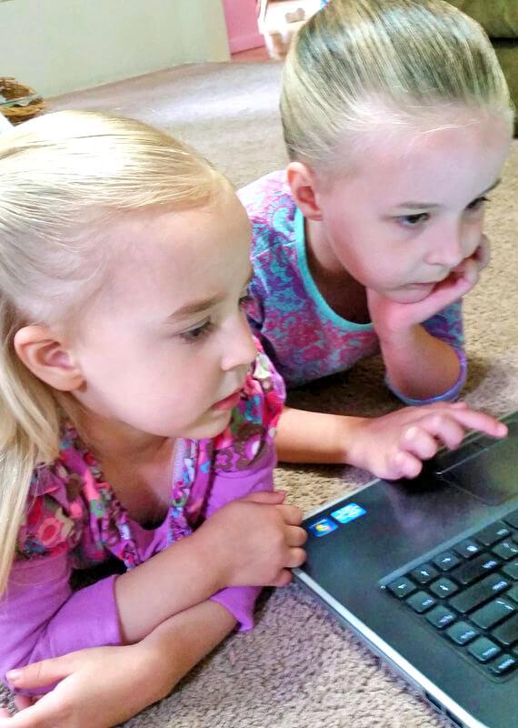 2 little girls using laptop for online reading lessons