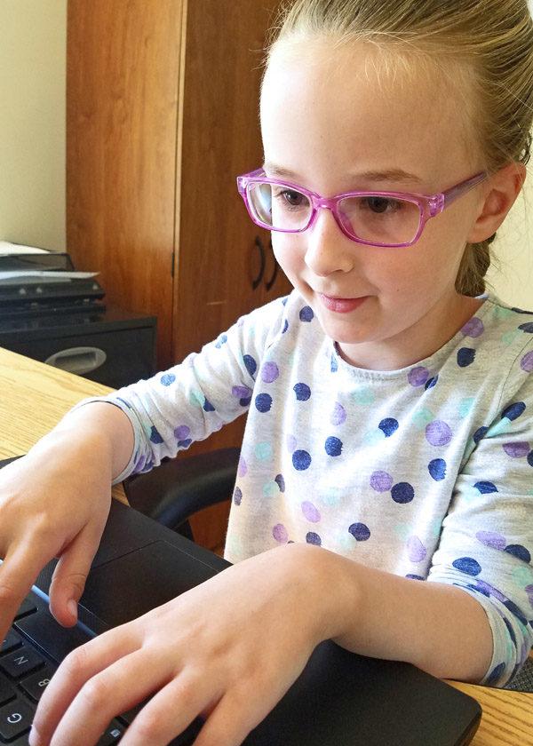 Girl practicing typing on laptop