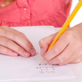 Little girl writing math problems on paper