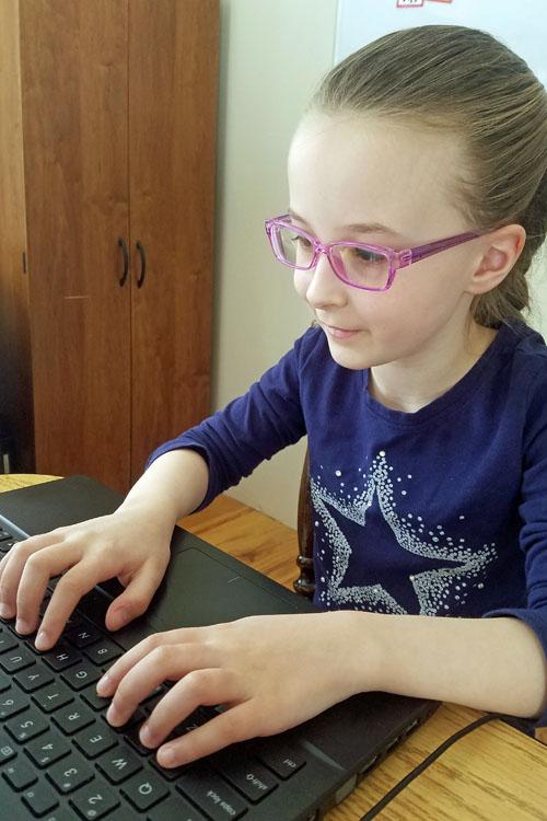 Smiling girl typing on keyboard