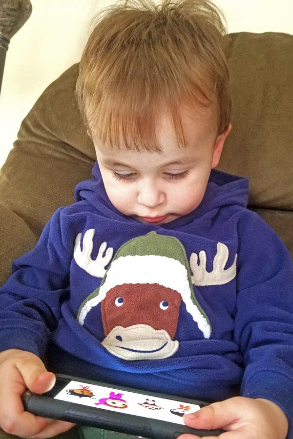 Little boy watching videos on an iPhone