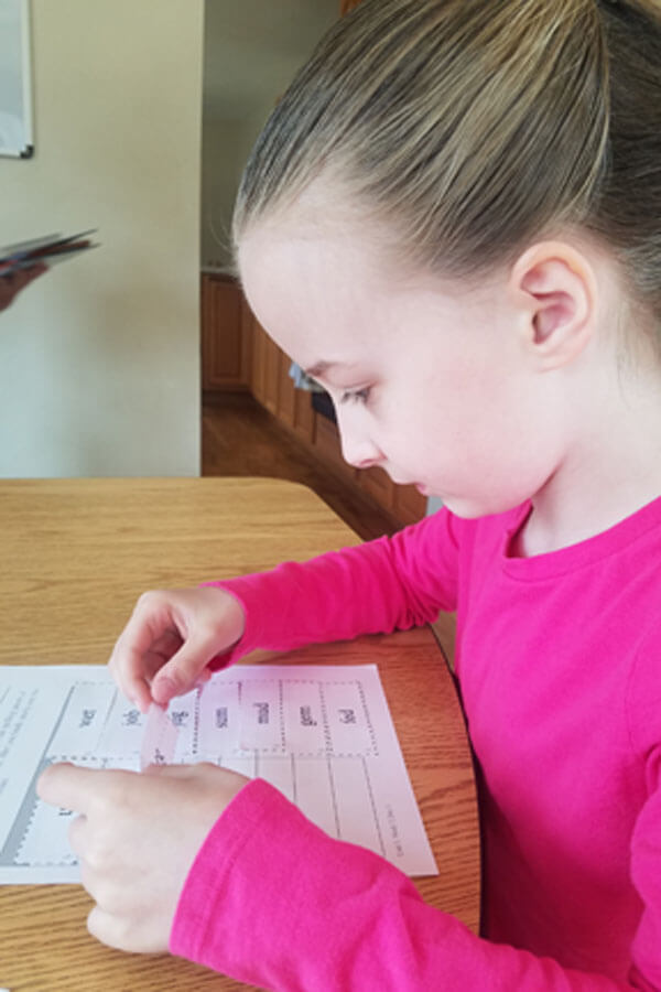 Young girl practicing spelling patterns at schoolroom table