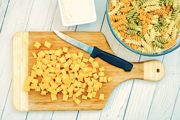 Cubes of cheese on a cutting board and a bowl of classic pasta salad on a white wooden table