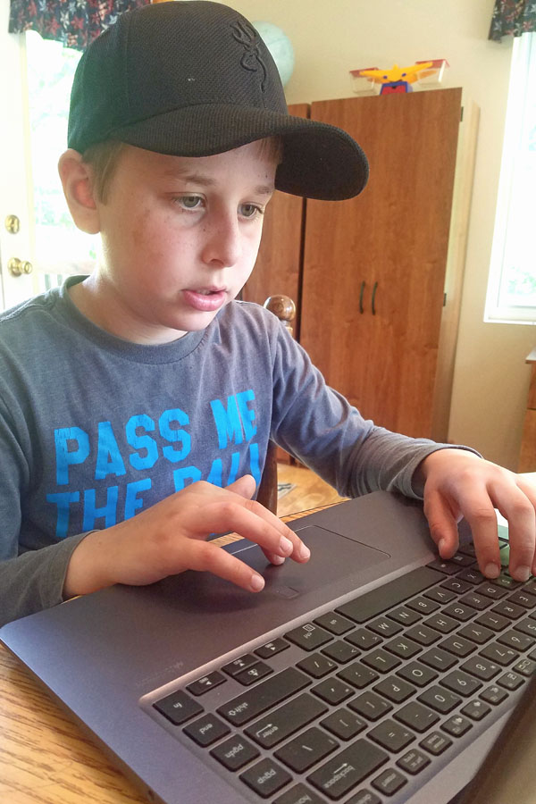 Boy using laptop to complete math curriculum