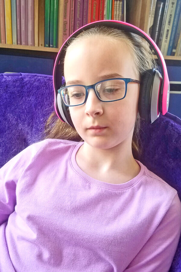 Young girl listening to living history stories with pink headphones