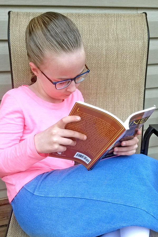 Young girl reading living book about the Vikings