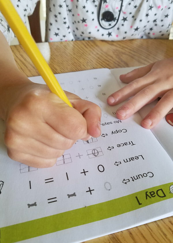 Child using a pencil to copy math facts in an addition workbook