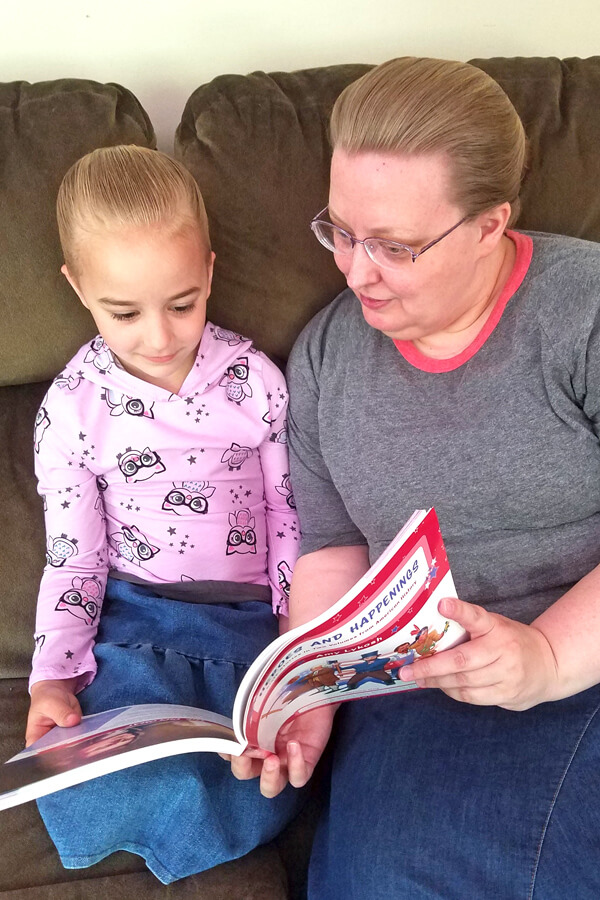 Mother and young daughter reading a colorful history book together
