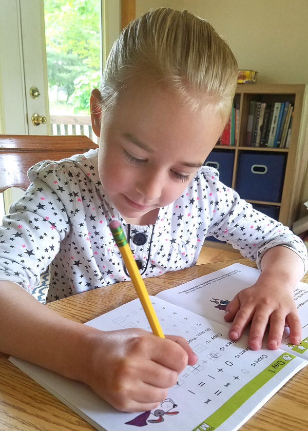 Little girl sitting at table writing math facts in an addition workbook