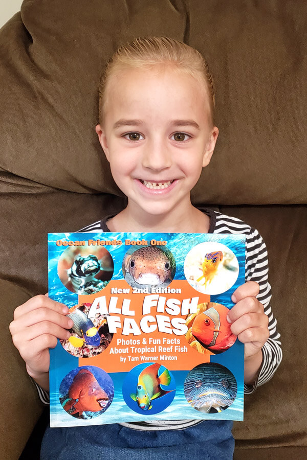 Smiling girl holding up colorful book entitled All Fish Faces