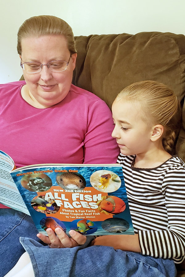 Mother and little girl reading a colorful book