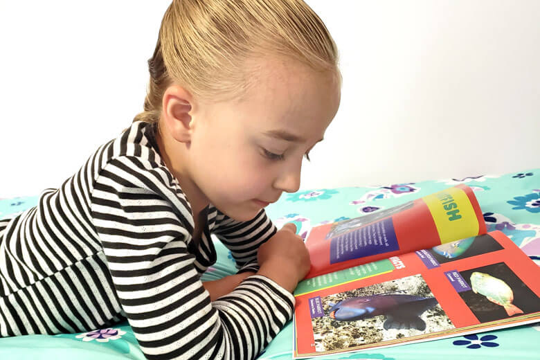 Little girl lying on bed reading a colorful book