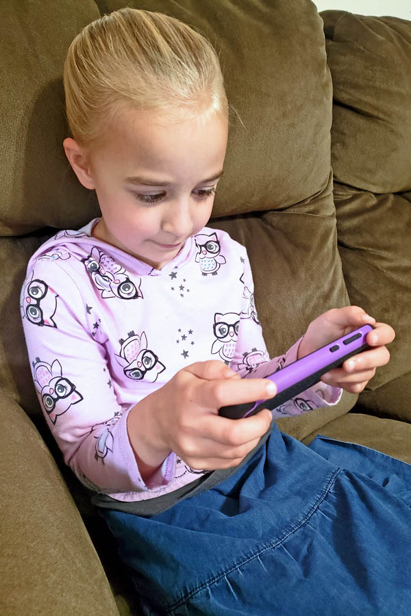 Young girl using smartphone to play online phonics game
