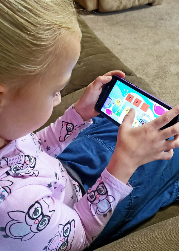 Young girl using educational phonics game on smartphone