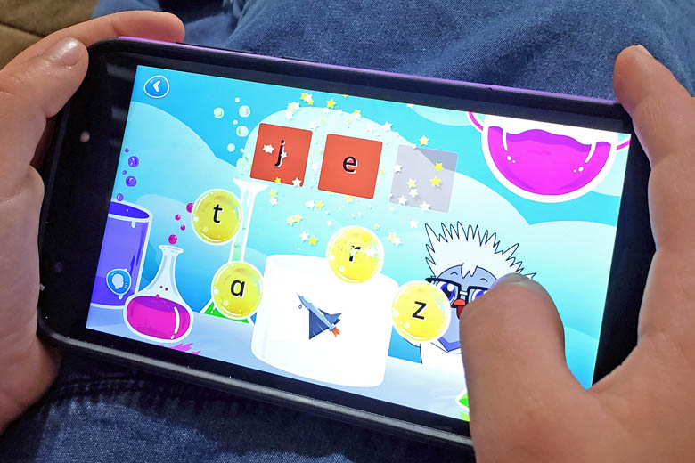 Child's hands holding smartphone with phonics game on screen