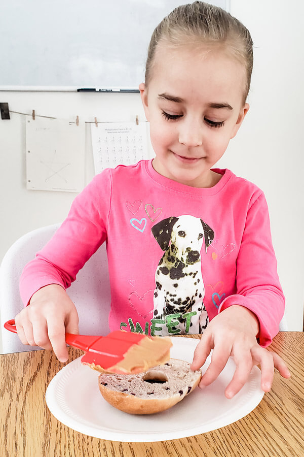 Young girl spreading peanut butter on a bagel to make a bird feeder
