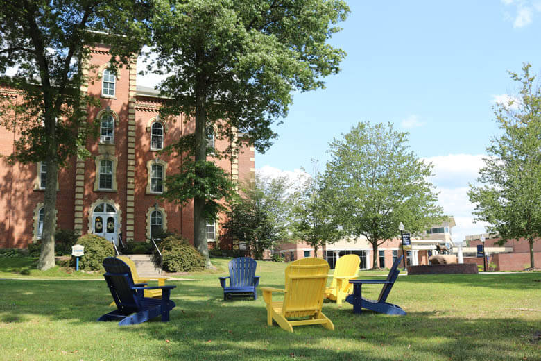 Colorful chairs on the lawn at Thiel College, with college buildings in the background