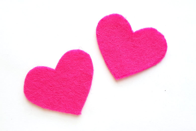 Two pink felt hearts lying on a white background