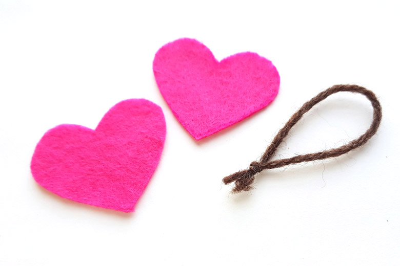 Two pink felt hearts and a loop of brown yarn lying on a white background