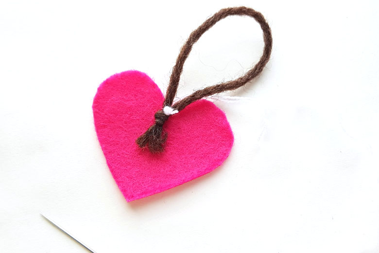 Pink felt heart sewing project lying on white background