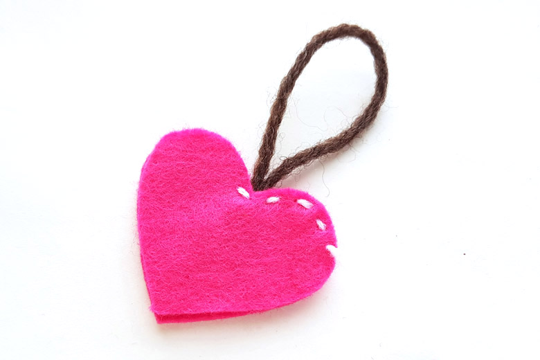 Two pink felt hearts partially stitched together with white thread