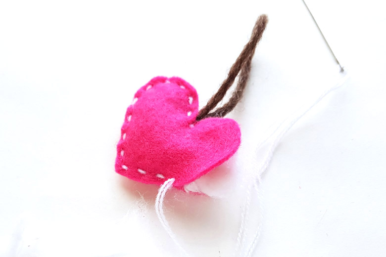 Partially stitched pink heart sewing project with needle and thread