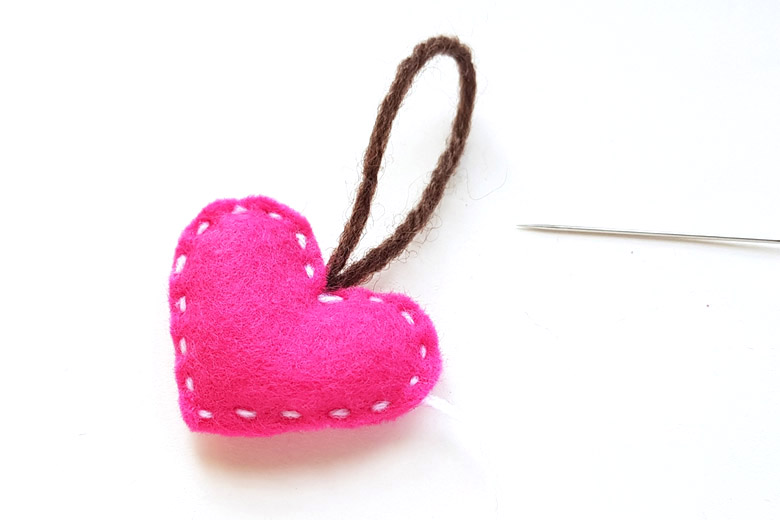 Stuffed pink felt heart with needle and thread lying on a white background