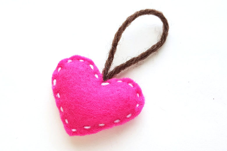Stuffed pink felt heart sewing project with brown yarn hanging loop