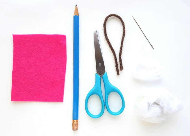 Pink felt, a pencil, scissors, needle, and thread for making a felt heart handicraft