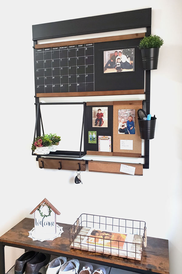 Wall organizer with blackboard and mirror hanging on white wall