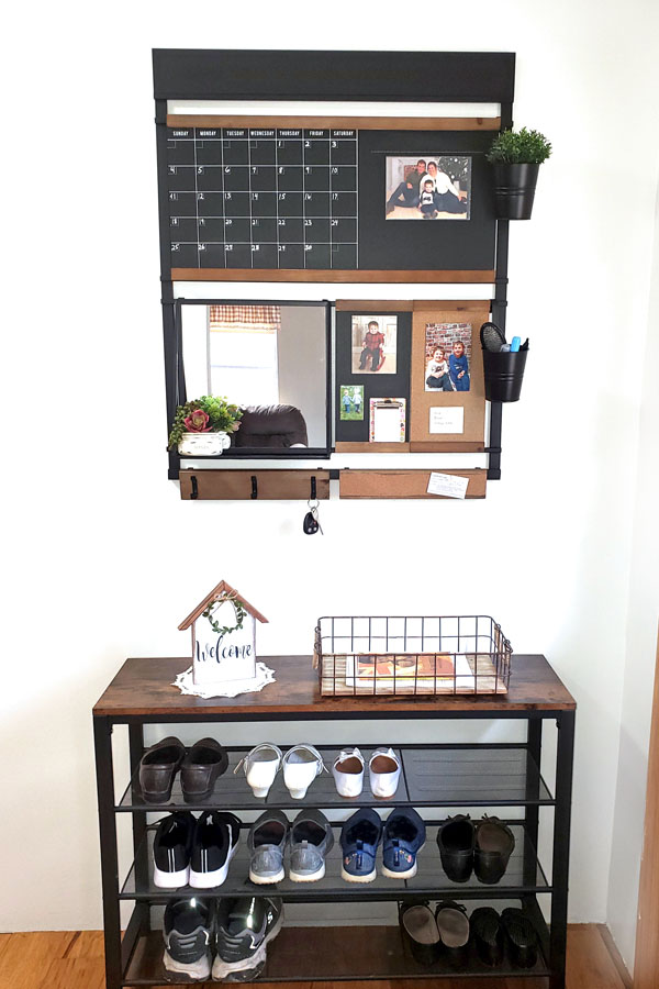 Wall organizer hanging on white wall above a shoe rack