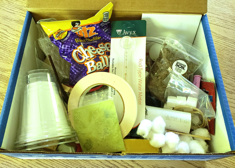 Open box filled with science experiment supplies