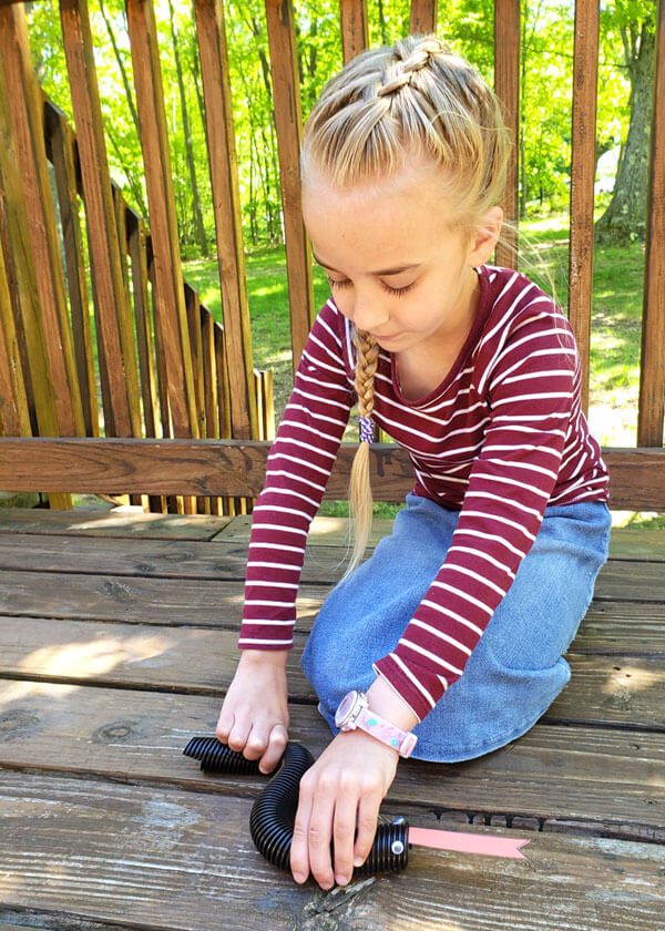 Young girl doing a hands-on science experiment with a black flexible pipe that looks like a snake