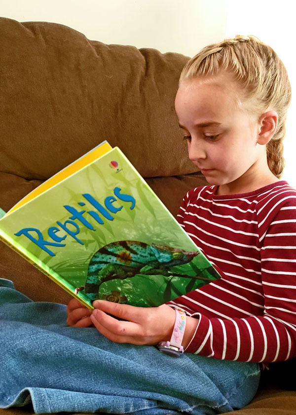 Young girl reading a science book about reptiles