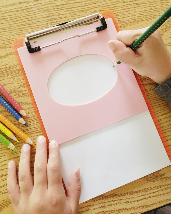 Child's hand tracing oval shape with colored pencil