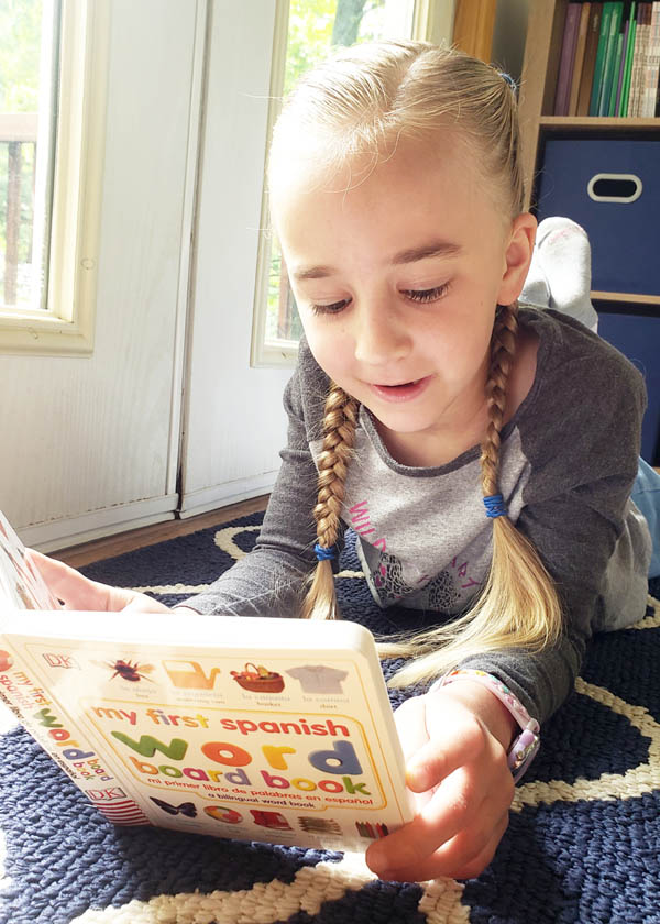 Young girl with long braids lying on stomach and reading colorful Spanish book