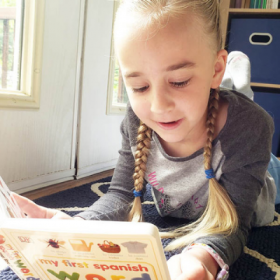 Young girl with long braids reading a book of Spanish words